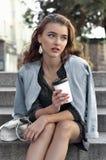 Flicka som rymmer ett exponeringsglas med en drink i hennes hand arkivfoton