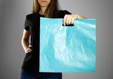 Flicka som rymmer ett ljust - blå plastpåse close upp Isolerad bakgrund royaltyfri fotografi