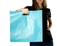 Flicka som rymmer ett ljust - blå plastpåse close upp Isolerad bakgrund fotografering för bildbyråer