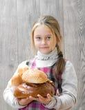 Flicka som rymmer mycket bröd Royaltyfria Foton