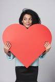 Flicka som rymmer stor röd hjärtaform Fotografering för Bildbyråer
