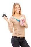 Flicka som rymmer två filmbiljetter och ask av popcorn Fotografering för Bildbyråer