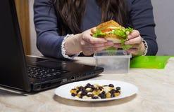 Flicka som rymmer upp en smörgås och ett arbete på en bärbar dator, slut, kalorier arkivfoton