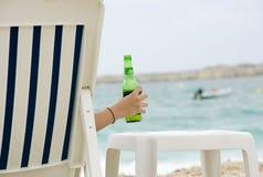 Flicka som rymmer uppfriskande kallt öl på stranden Arkivfoto