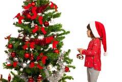Flicka som sätter färgrika bollar i träd royaltyfri bild