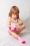 flicka som sätter lilla sockor Arkivfoto