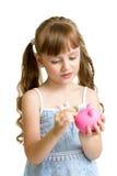 Flicka som sätter myntet in i spargrisen arkivbild
