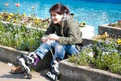flicka som sätter rollerblades Fotografering för Bildbyråer