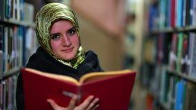 Flicka som söker för böcker arkivfilmer