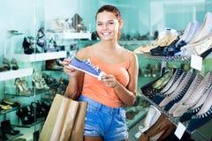 Flicka som söker för par av nya skor Royaltyfri Bild