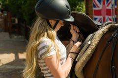 Flicka som sadlar hästen Arkivbild