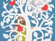 Flicka som ser över ett dekorativt träd Arkivfoto