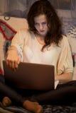Flicka som ser bärbara datorn Royaltyfri Bild