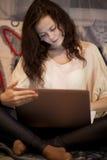Flicka som ser bärbara datorn Royaltyfria Bilder
