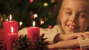 Flicka som ser brinnande stearinljus, lycklig barndom och tro i julmirakel lager videofilmer