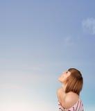 Flicka som ser copyspacen för blå himmel Arkivbild