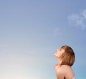 Flicka som ser copyspacen för blå himmel Arkivbilder