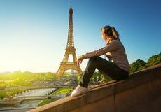 Flicka som ser Eiffeltorn i soluppgångtid royaltyfri foto