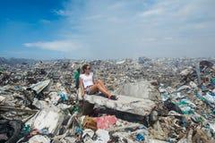 Flicka som ser en sida bland berg av avfall på avskrädeförrådsplatsen arkivbild