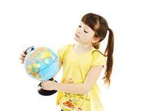 Flicka som ser ett jordklot Arkivbild
