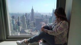 Flicka som ser fr?n skyskrapa p? Manhattan i New York lager videofilmer