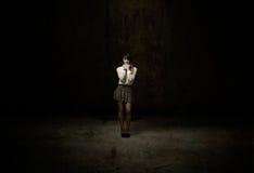 Flicka som ser i ett mörkt rum fotografering för bildbyråer
