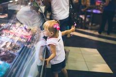 Flicka som ser i fönstret med glass Arkivfoton