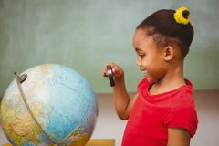 Flicka som ser jordklotet till och med förstoringsglaset Royaltyfri Bild