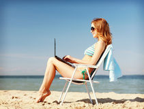 Flicka som ser minnestavlaPC på stranden Royaltyfri Bild