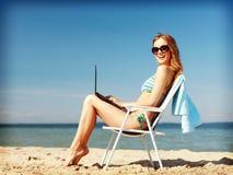 Flicka som ser minnestavlaPC på stranden Royaltyfri Fotografi