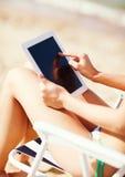 Flicka som ser minnestavlaPC på stranden Royaltyfri Foto