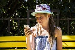 Flicka som ser mobiler Fotografering för Bildbyråer