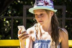 Flicka som ser mobiler Arkivbilder