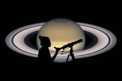 Flicka som ser stjärnorna med teleskopet Saturn planet Royaltyfri Fotografi