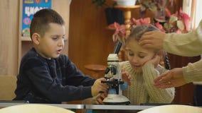 Flicka som ser till och med ett mikroskop lager videofilmer