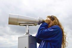 Flicka som ser till och med ett teleskop Arkivbilder