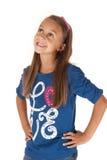 Flicka som ser upp med händer på höfter i blå skjorta Fotografering för Bildbyråer
