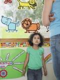 Flicka som ser upp på läraren In Class Royaltyfri Foto