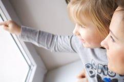Flicka som ser ut ur fönster Arkivfoton
