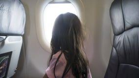 Flicka som ser utanför från flygplanfönster Arkivfoto