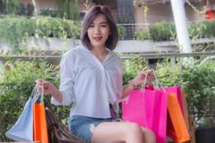 Flicka som shopping, lyckliga flickas på trevliga ferie, asiatisk flickas hållande shoppa påsar arkivfoton