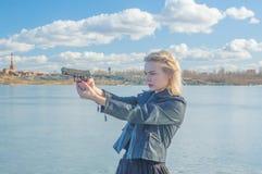 Flicka som siktar en pistol på bakgrunden av sjön Royaltyfri Bild