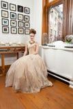 Flicka som sitter den lyxiga klänningen Arkivfoto
