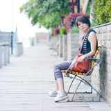 Flicka som sitter i den utomhus- stolen Arkivfoton
