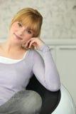 Flicka som sitter i fåtölj Royaltyfria Bilder