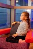 Flicka som sitter i stol i kabin i ship arkivfoto