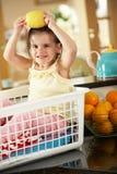 Flicka som sitter i tvättkorg med citronen Royaltyfri Foto