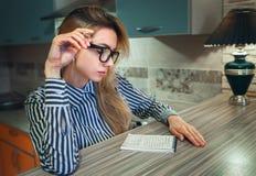 Flicka som sitter lampetter för hem- miljö och hänsynsfullt ser in i den pappers- anteckningsboken Royaltyfria Foton