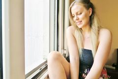 flicka som sitter nära fönstret och gulligt le arkivfoto