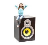 Flicka som sitter på en musikalisk högtalare Royaltyfri Bild